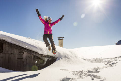 Woman jumping off the roof of a cabin into the deep snow - DHEF00257