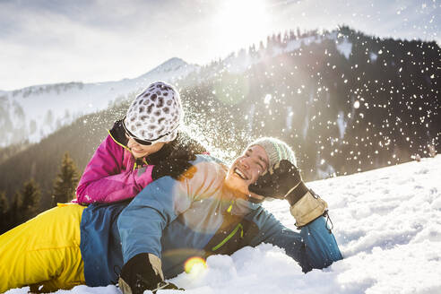 Carefree couple lying in snow - DHEF00272