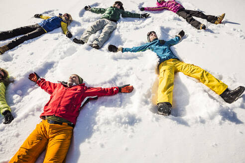 Group of friends lying in snow - DHEF00284