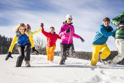 Group of carefree friends running and having fun in snow, Achenkirch, Austria - DHEF00299
