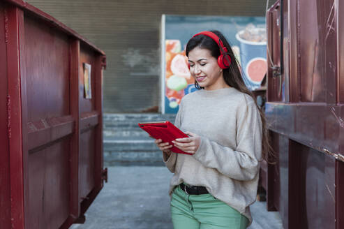 Smiling young woman listening music on headphones while holding digital tablet - JMPF00320