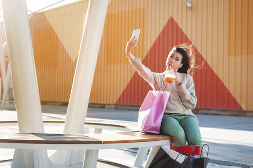 Pretty woman clicking selfie while sipping juice at shopping mall - JMPF00326