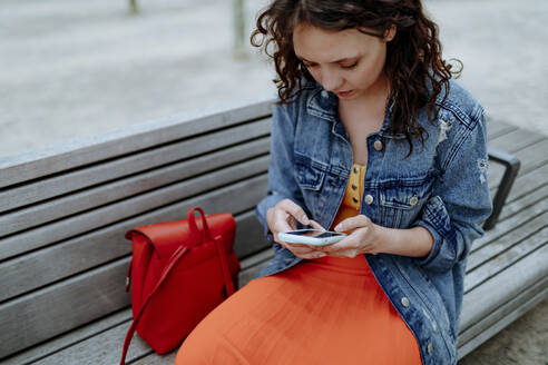 Young woman using smartphone sitting on bench - OGF00467