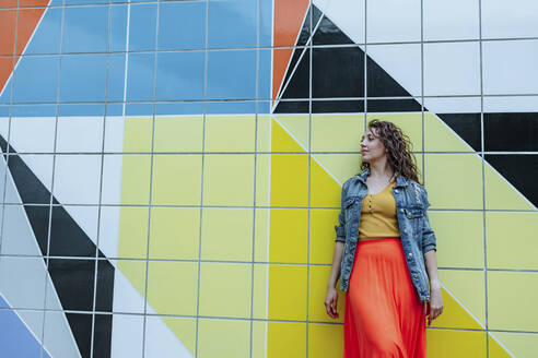 Young woman leaning on colorful tiled wall looking sideways - OGF00479