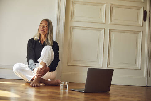 Thoughtful woman by laptop sitting on floor at home - MCF01046