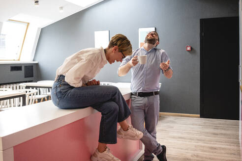 Cheerful businessman and businesswoman enjoying coffee break at cafeteria in coworking space - VPIF02699