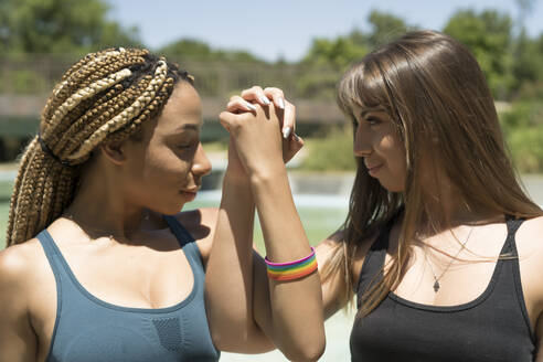 Lesbian couple enjoying a day in the park holding hands - CAVF88285
