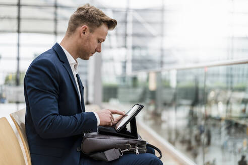 Businessman with bag using digital tablet while sitting in city - DIGF12855