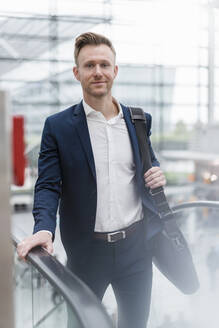 Confident businessman with bag walking by escalator in city - DIGF12861