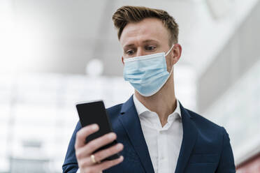 Businessman using mobile phone while wearing face mask in city - DIGF12891