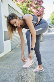 Smiling woman tying shoelace at sidewalk - KIJF03210