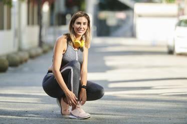 Smiling woman with headphones tying shoelace at sidewalk - KIJF03216