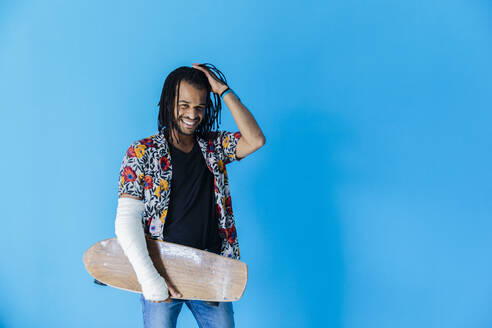 Smiling man with fractured arm holding skateboard against blue background - MRAF00576
