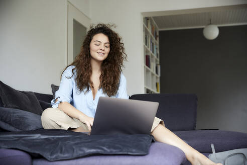 Young woman working while using laptop and sitting on sofa at home - FMKF06252