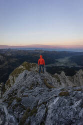Rear view of hiker on viewpoint during sunrise, Gimpel, Tyrol, Austria - MALF00059