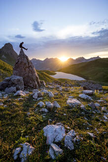 Hiker sitting on rock during sunset at Lake Rappensee, Bavaria, Germany - MALF00071