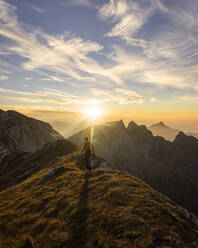 Female hiker walking to viewpoint during sunset, Hochplatte, Bavaria, Germany - MALF00080