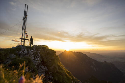 Hiker standing on viewpoint during sunset, Brentenjoch, Bavaria, Germany - MALF00092
