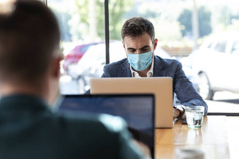 Businessman wearing protective face mask while using laptop in cafe during coronavirus outbreak - JSRF01038