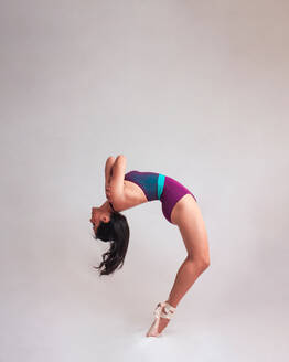 Side view of graceful woman in leotard and pointe shoes bending back while dancing against gray background - ADSF11043