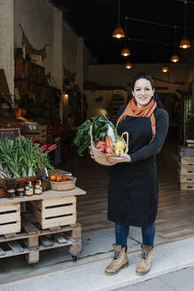 Smiling saleswoman holding vegetable basket while standing at store entrance - RDGF00057