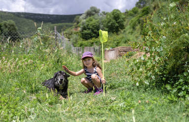Little girl with a butterfly hunter and a dog in the middle of nature. Barcelona, Spain - GEMF04075