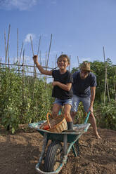 Father and daughter having fun with the wheelbarrow in garden - VEGF02688