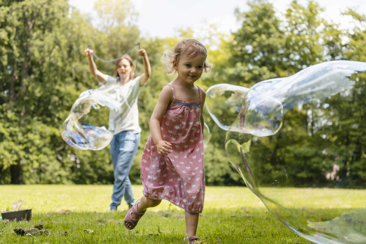 Baby girl running after bubble with mother standing in background at park - DIGF12906 - Daniel Ingold/Westend61