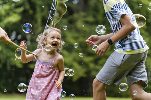 Cheerful girl enjoying with brother while running amidst bubbles at public park - DIGF12921