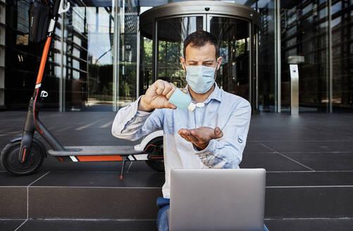 Entrepreneur with laptop sanitizing hands on staircase during coronavirus - VEGF02738