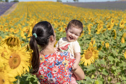 Mother carrying cheerful daughter in sunflower field during summer - GEMF04084