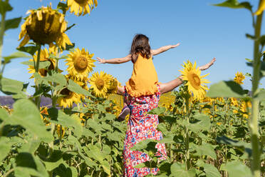 Mother carrying daughter on shoulders in sunflower field against clear sky - GEMF04087