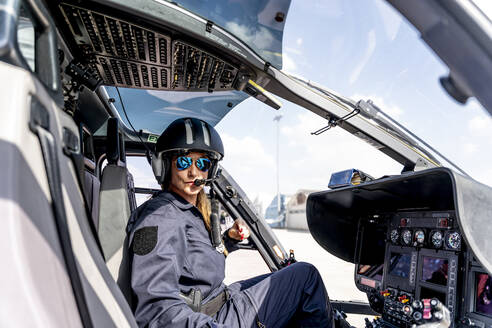 Female police pilot wearing sunglasses in helicopter - OCMF01638