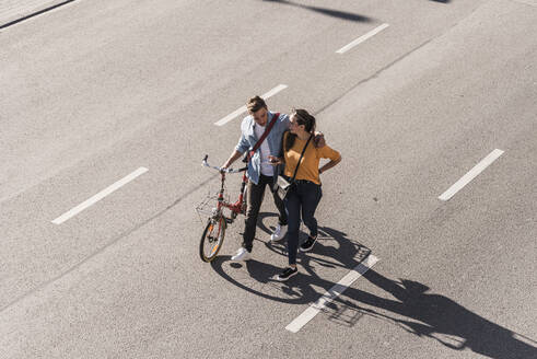Young couple with bicycle walking on street in city - UUF20868