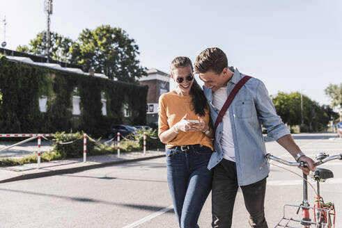 Cheerful young couple looking at smartphone while walking on street in city - UUF20871