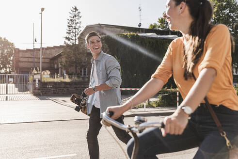 Cheerful young man looking at girlfriend riding bicycle on street in city during sunny day - UUF20874