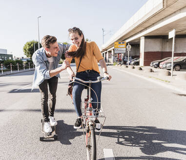Playful boyfriend skateboarding while girlfriend riding bicycle on street in city - UUF20877