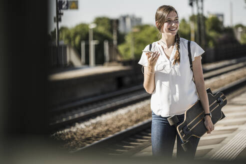 Smiling beautiful woman with skateboard looking away while walking at railroad station - UUF20889