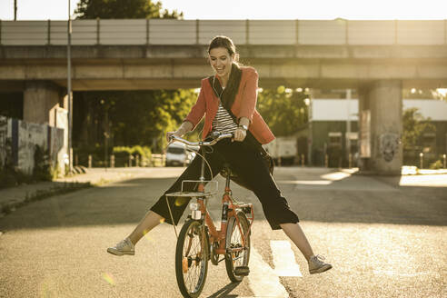 Cheerful young woman enjoying cycling on street during sunny day - UUF20931