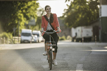 Smiling young woman riding bicycle on street in city - UUF20934