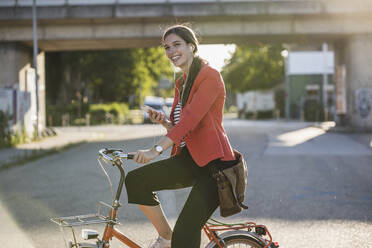 Happy young woman using smart phone while riding bicycle on street in city - UUF20937