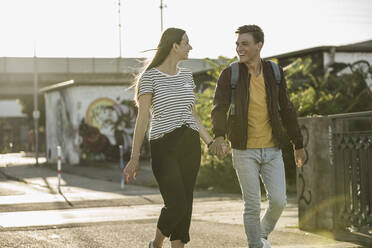 Happy young couple holding hands while walking on street - UUF20940