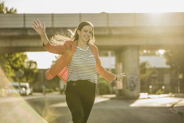 Carefree woman running with arms outstretched on street during sunny day - UUF20943