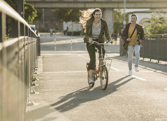 Boyfriend running behind happy girlfriend riding bicycle in city on sunny day - UUF20946