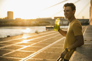Man with water bottle after workout against clear sky - UUF20970