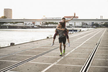 Smiling man giving piggyback ride to woman at harbor - UUF20994
