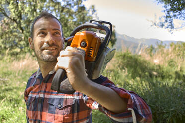 Smiling male lumberjack carrying electric saw on shoulder in forest - VEGF02764