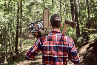 Lumberjack with chainsaw and axe walking in forest - VEGF02779