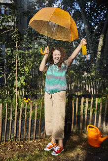 Cheerful woman with mouth open holding bottle and umbrella while standing at back yard enjoying sunny day - FMKF06284