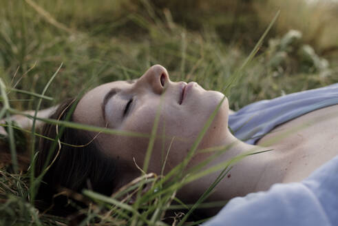 Beautiful woman relaxing with eyes closed on grass - DSIF00090